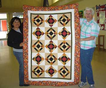 Staff accept quilt donated by SRQG.