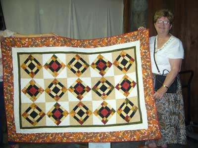 Pam Beebe presents quilt to The Living Room